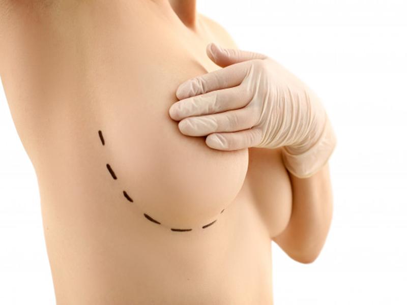 female-hand-gloves-holding-breast